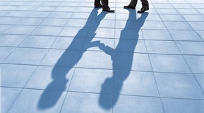 Shadow of buisnessmen shaking hands.